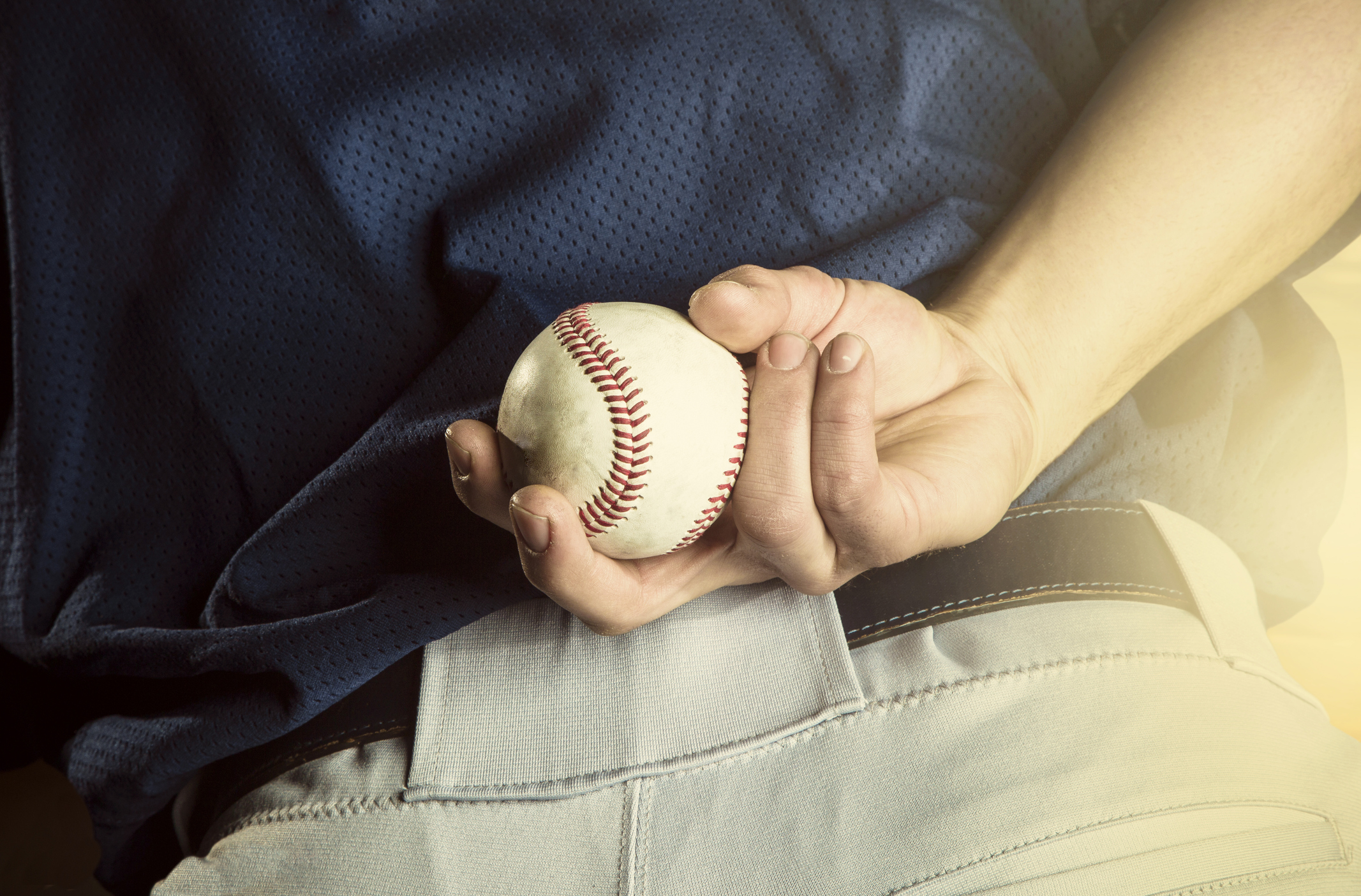 A close up view of the baseball pitchers hand just before throwing a fastball in a game. Focus on the fingers and the ball