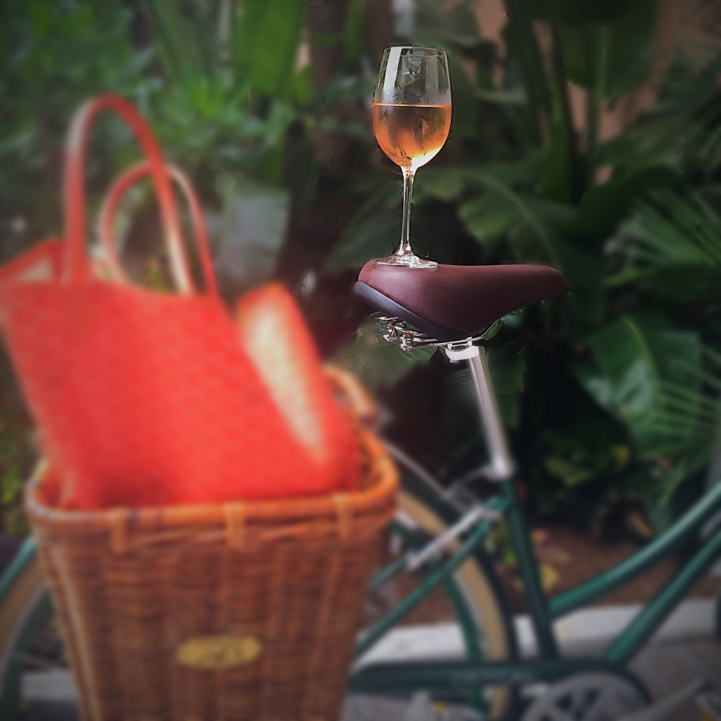 A glass of rosé is balanced on a bike seat, with a big orange bag in the back basket of the bike.