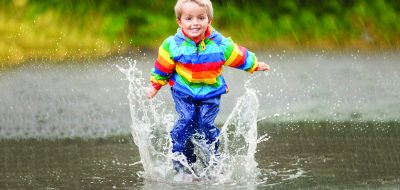 Keep Kid Entertained During rain — A kid jumping up and down in a puddle