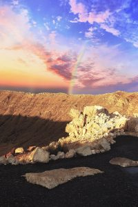 Sun on the horizon overlooking a mammoth impact crater in the desert