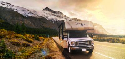 RV Leaks and Shaky Fivers -- RV on a highway winding through snow-capped mountains