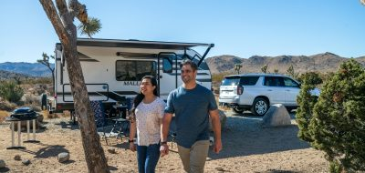 Taking your new RV out -- A couple embarks on a stroll through their campsite.