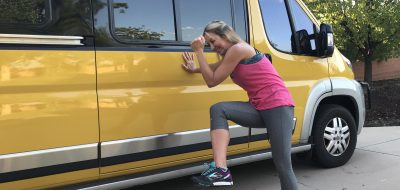 Woman stretches on the side of a Class B camper