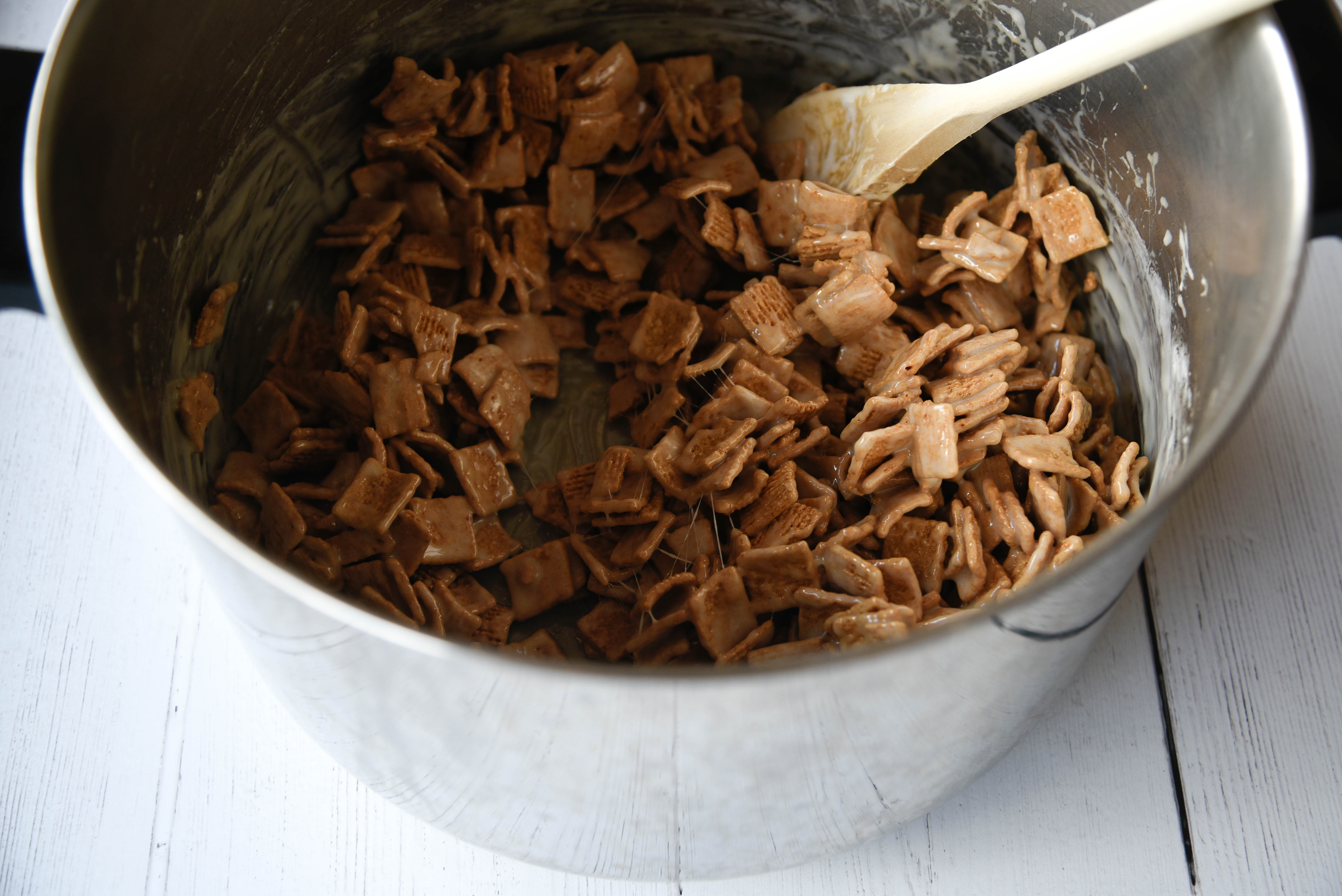 Cereal stirred into a pot with a wooden spoon