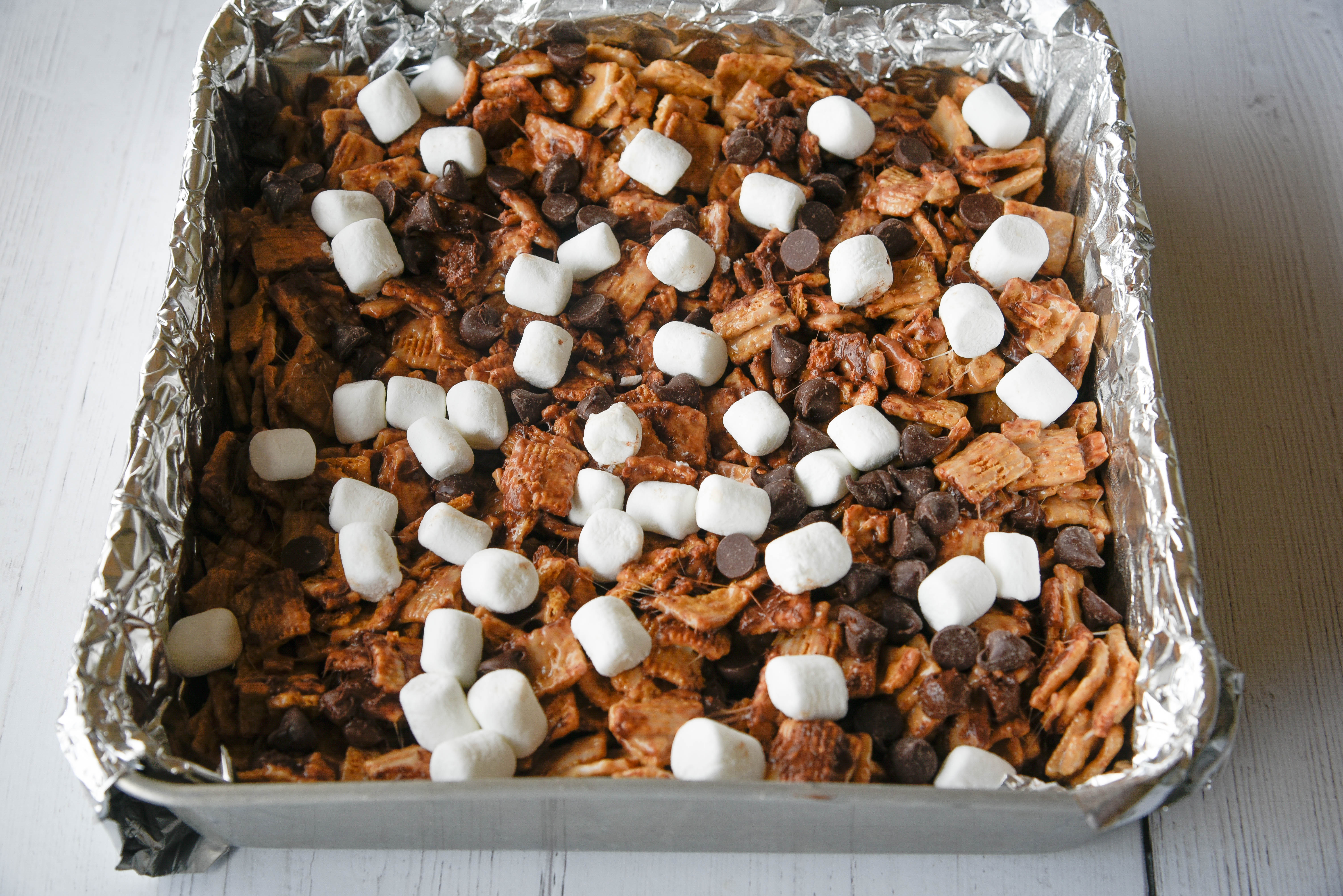 cereal, marshmallows and chocolate chips in a foil-lined pan.