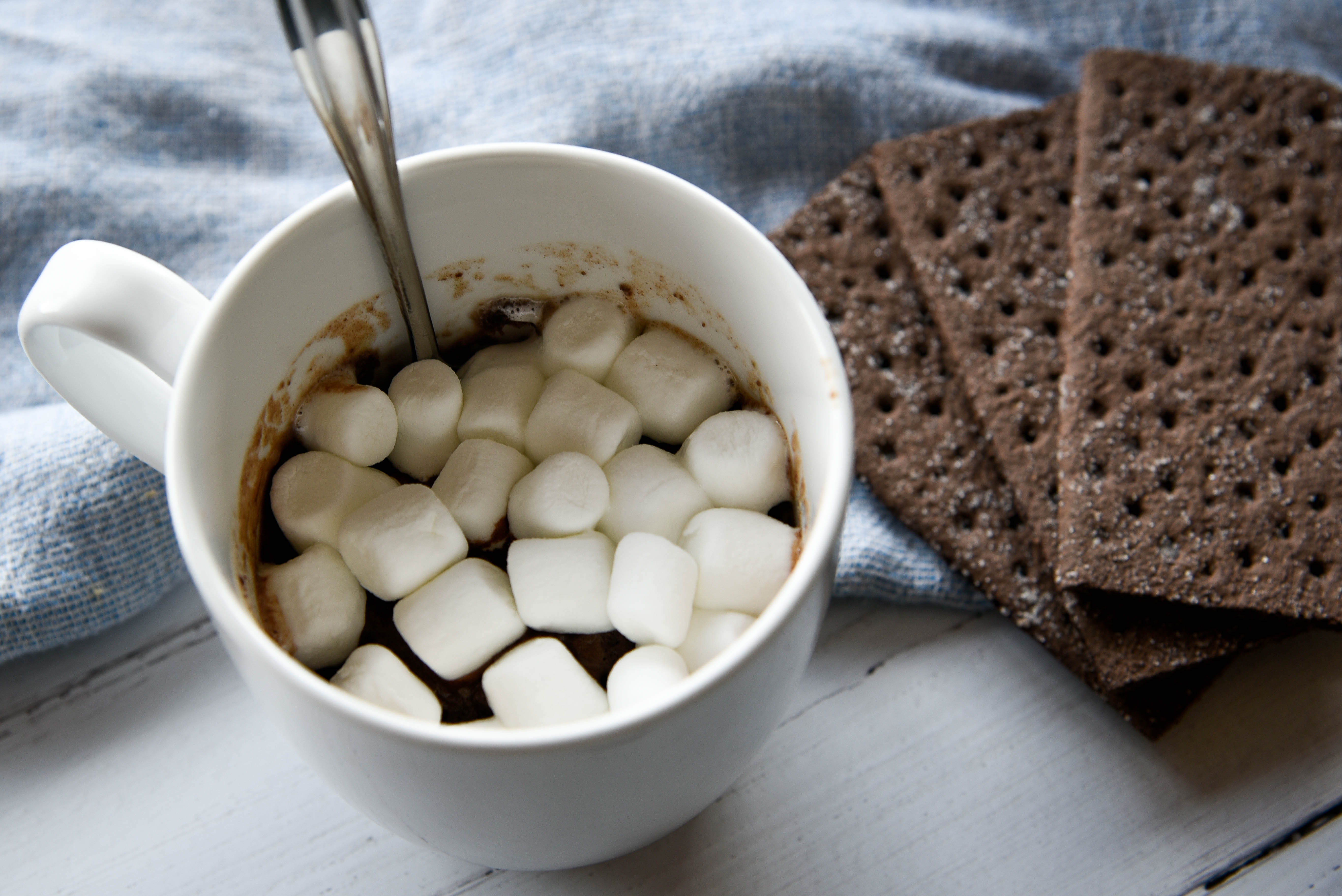 Spoon dipped into a cup of Marshmallows.