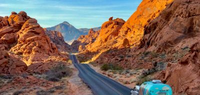 A colorful Airstream trailer is towed on a highway lined with red rock formations.