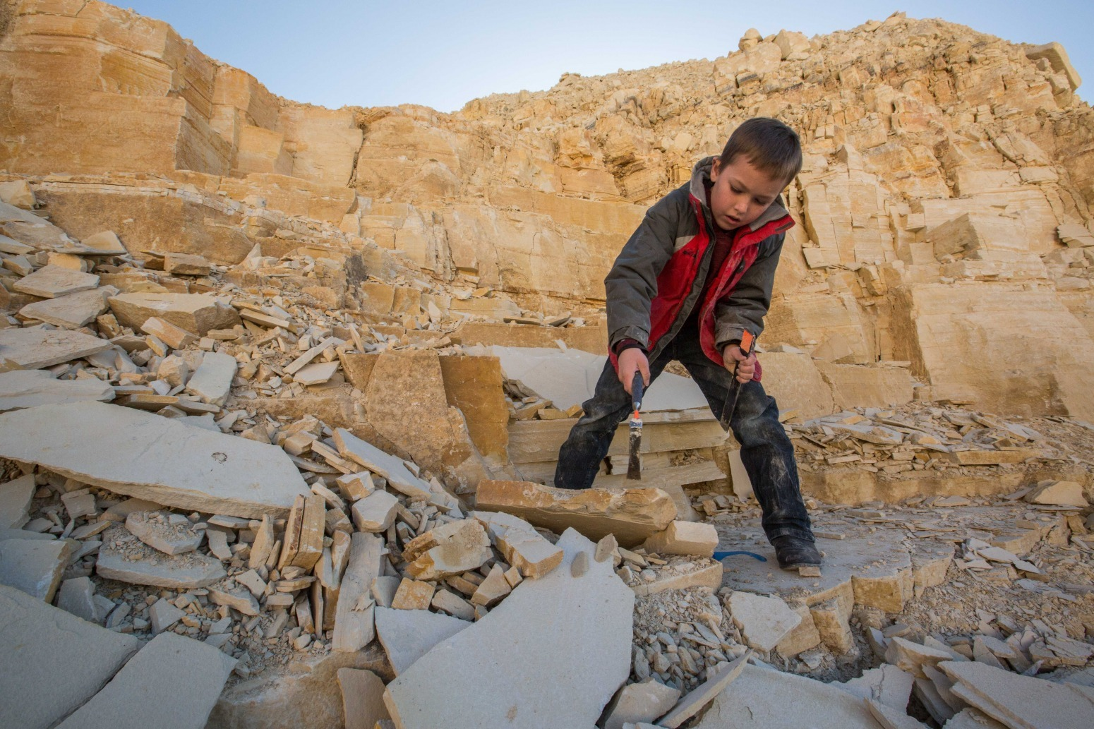 Western Wyoming itinerary —A boy chips away at a rock with a hammer at an archeological dig.