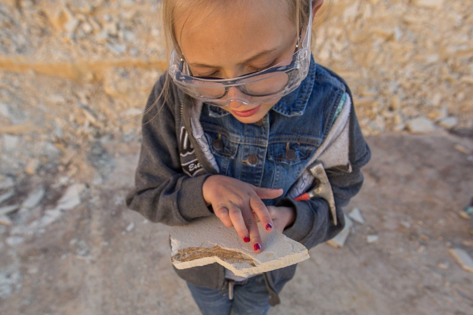 A girl examines a piece of chipped rock.