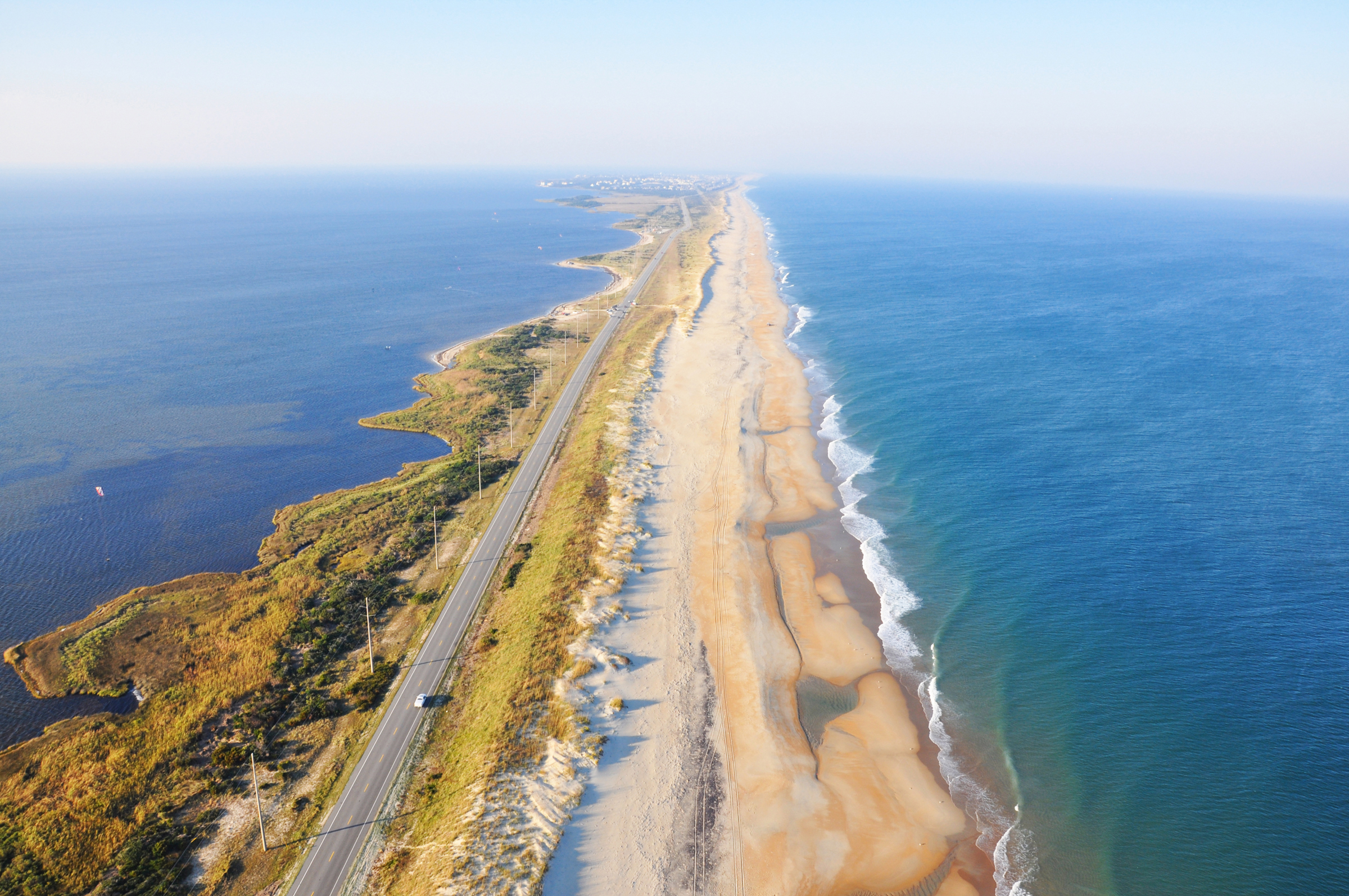 Aerial shot of a long, sandy strip of land surrounded by ocean on both sides.