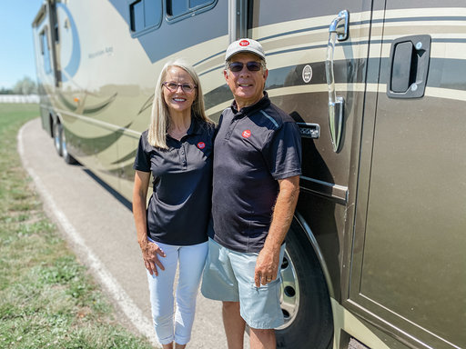 A man and woman standing on front of motorhome.