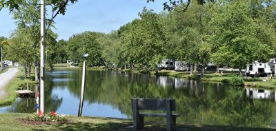 RV campground reflected on a placid pond.