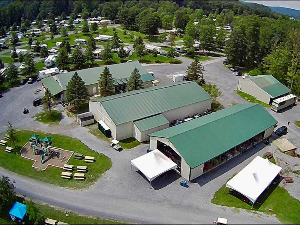 Aerial shots of manufactured campground buildings with RV spaces and playground visible.