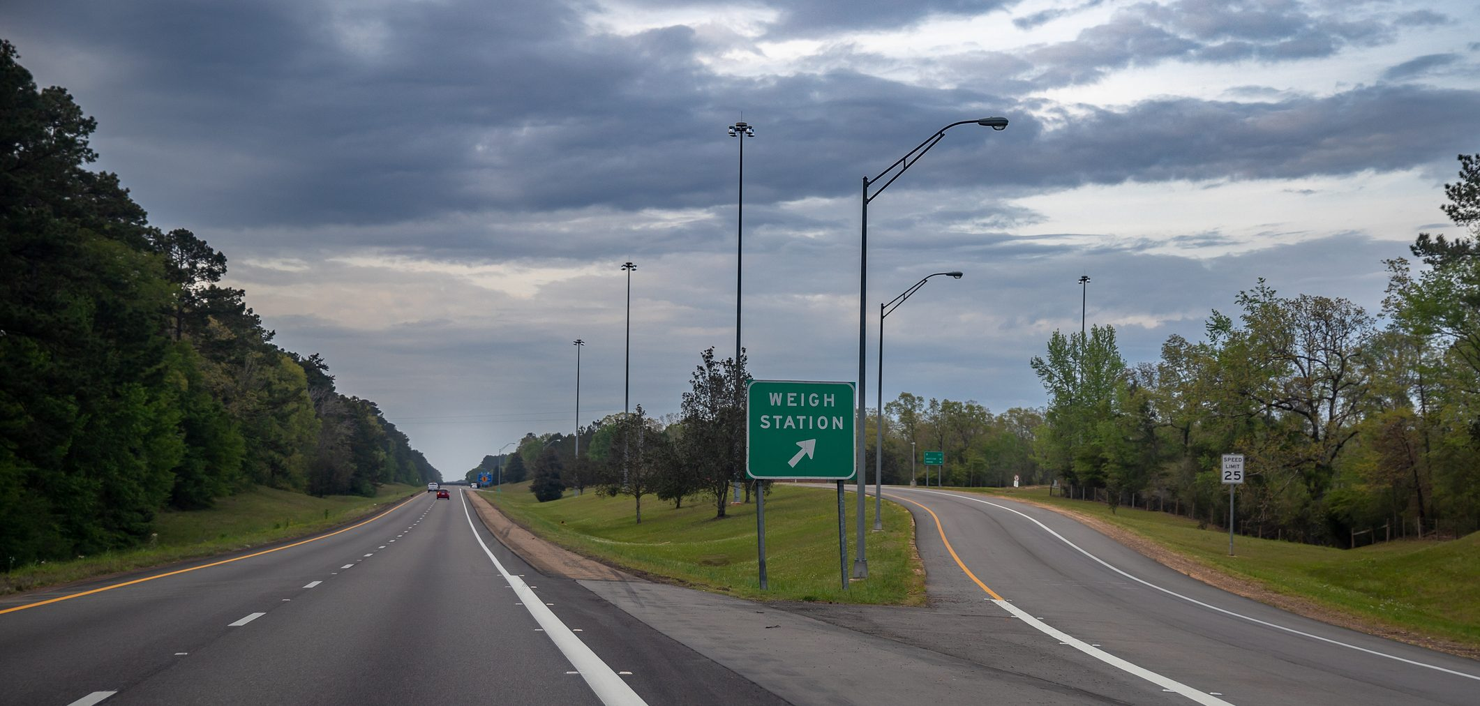 A sign for a weight scale on a highway offramp.