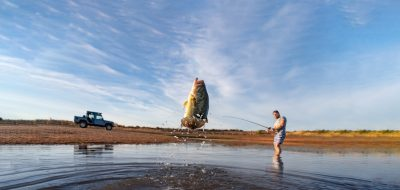 Man angling for bass in shallow water