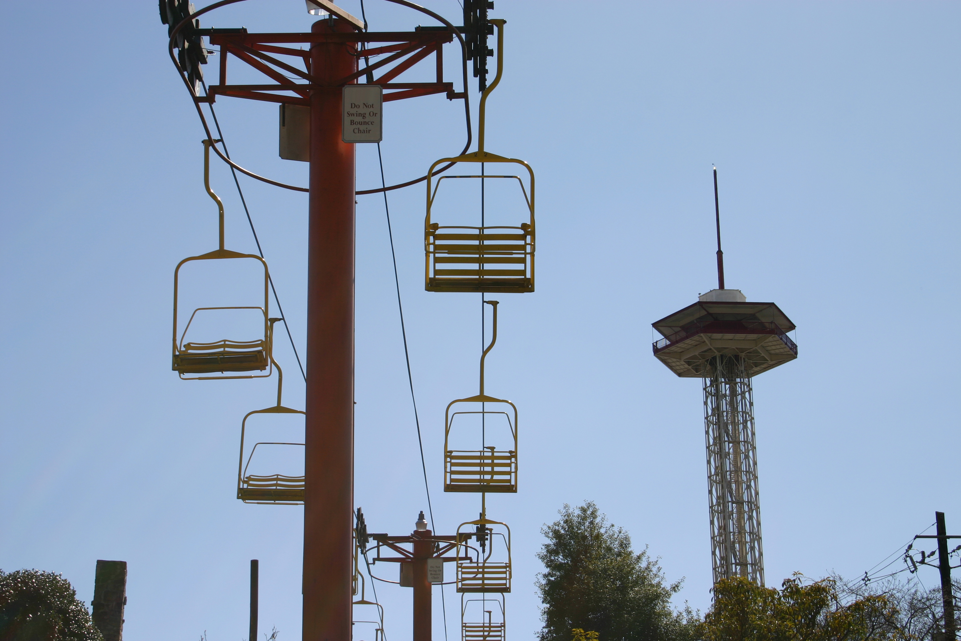 Chairlifts with tall tower in background.