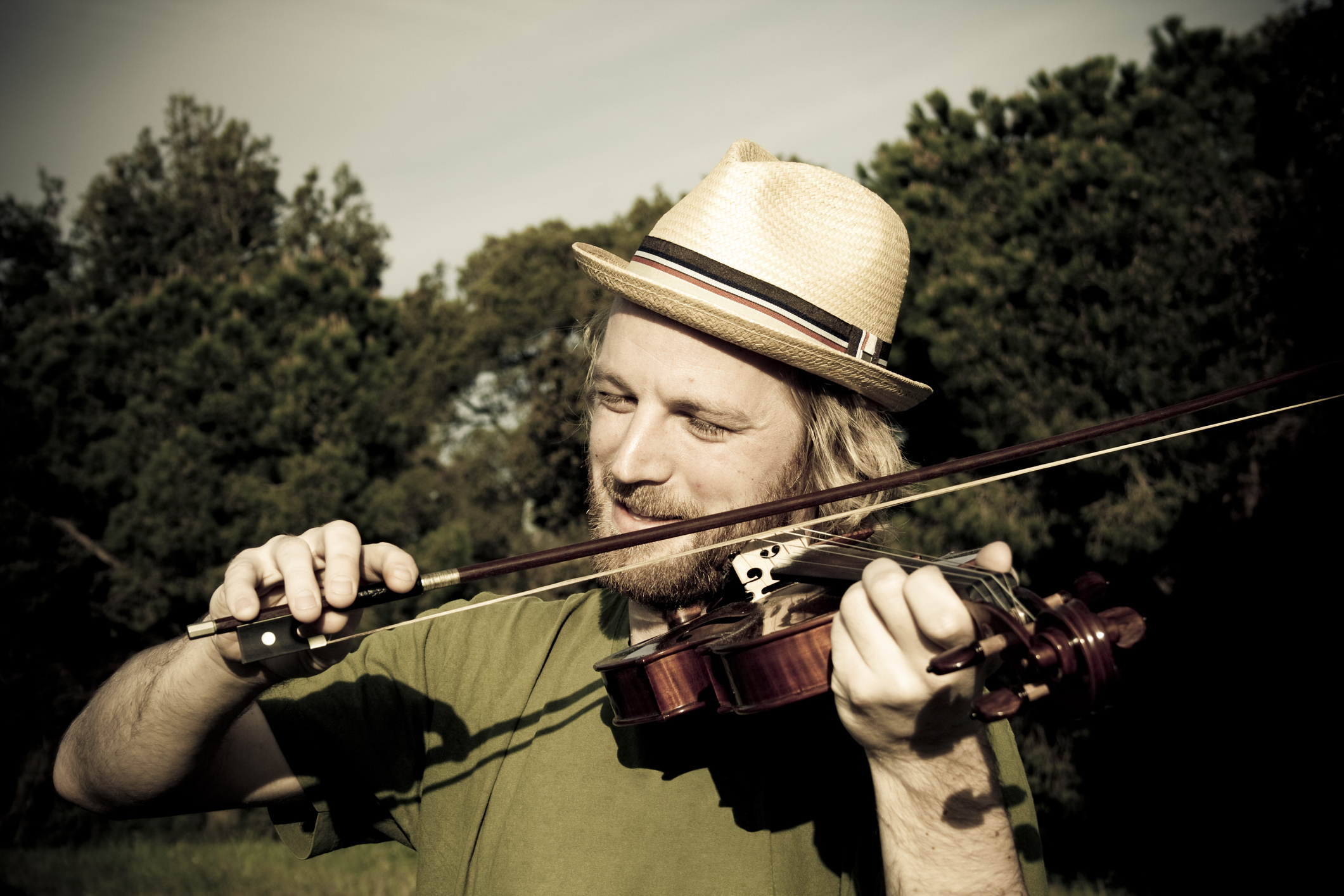 Man playing fiddle in a forested area.
