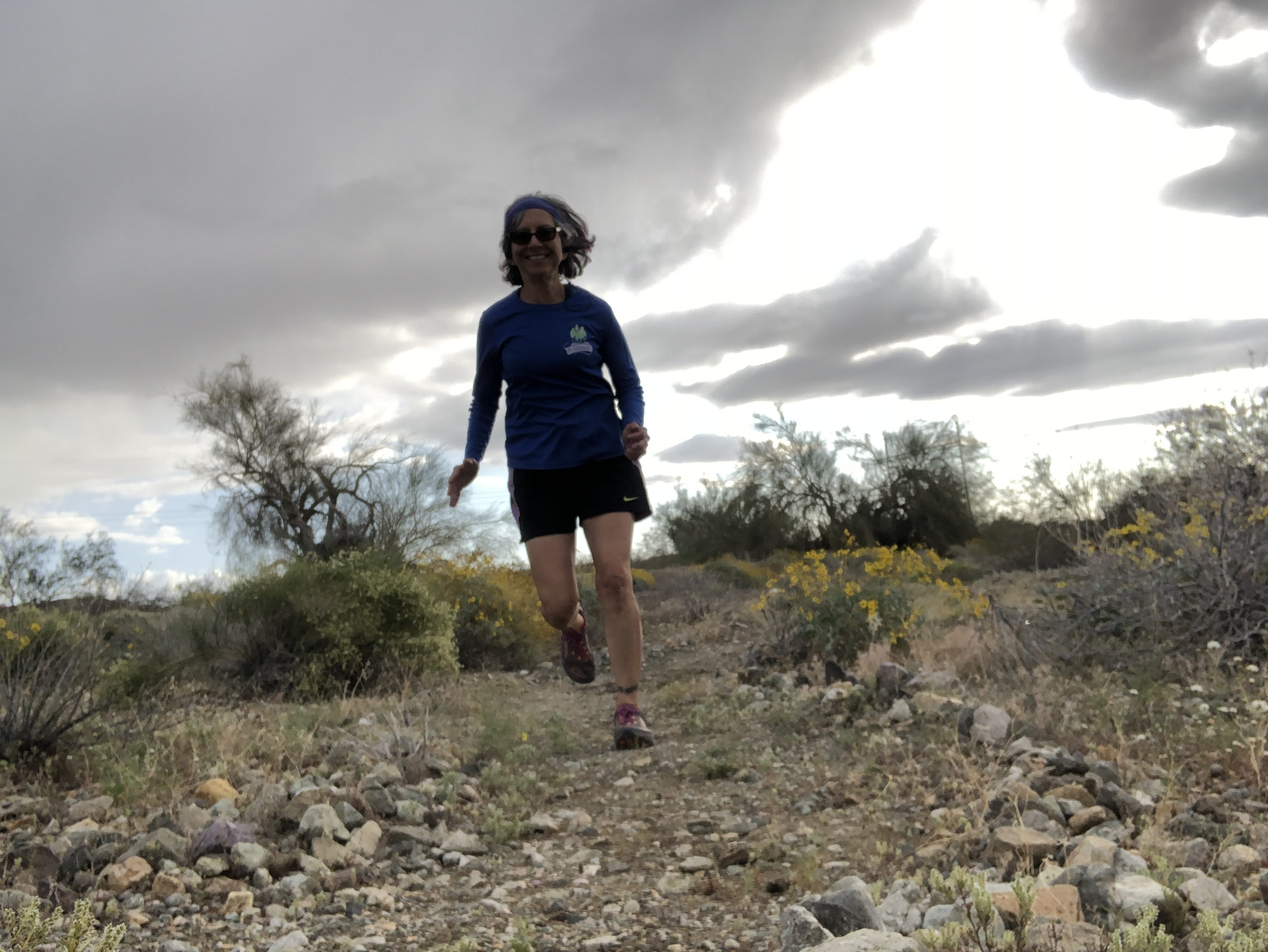 A woman running down a trail under gray skies.