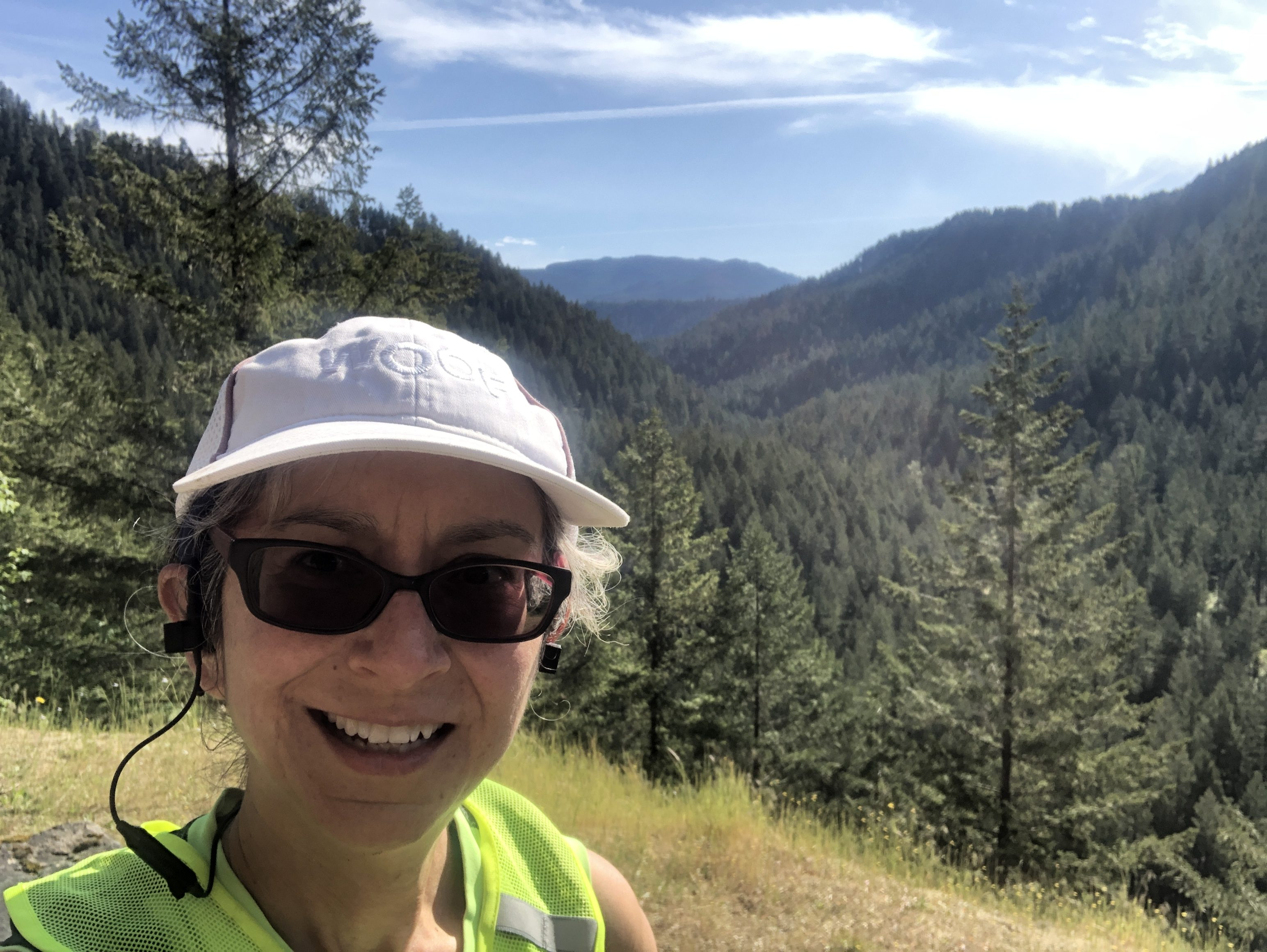 A woman in white cap smiling at camera with lush forest valley in backgound.