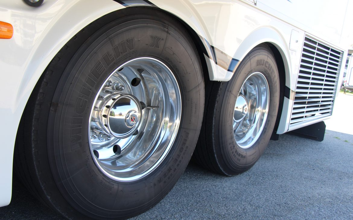 Low shot of tag axle-tires of motorhome on blacktop.