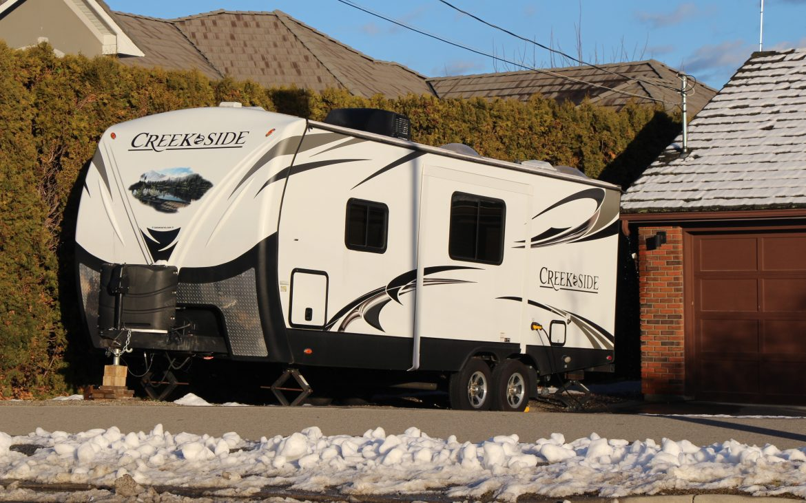 Fifth-wheel trailer parked in driveway near melting snow.