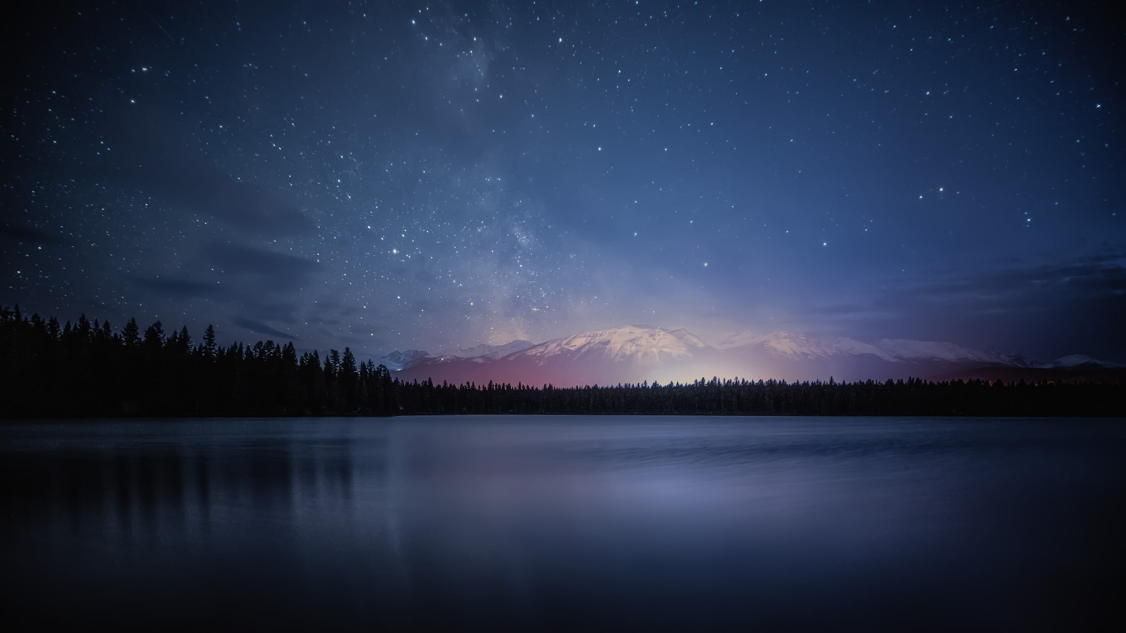 Stars twinkle above a sprawling and calm lake.