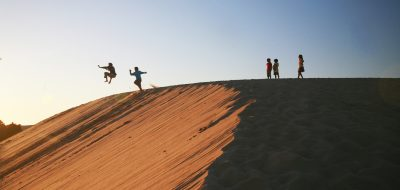 Wander North Carolina's Outer Banks —People jumping off a huge sand dune.