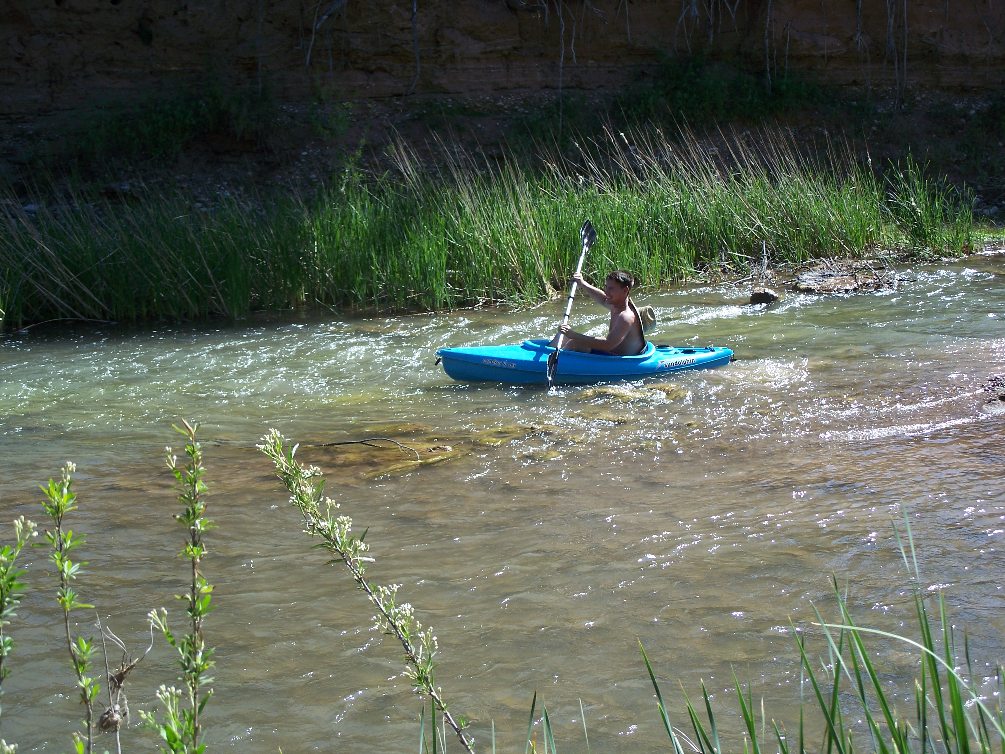 A young mand paddling a kayak down a small but fast-moving river.