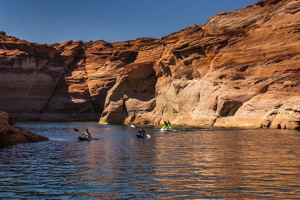 Kayakers paddle on a channel formed by two high rock walls.