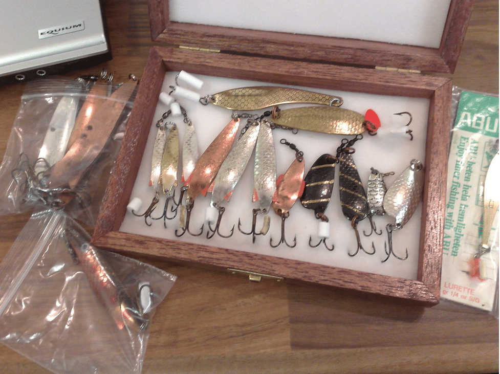 An array of shiny bass lures in spoon shape.