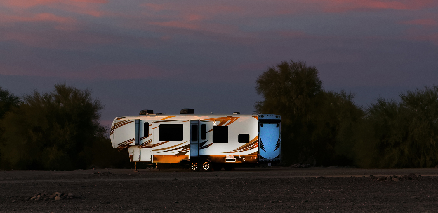selecting a vehicle to tow — A toy hauler trailer on a field at dusk.