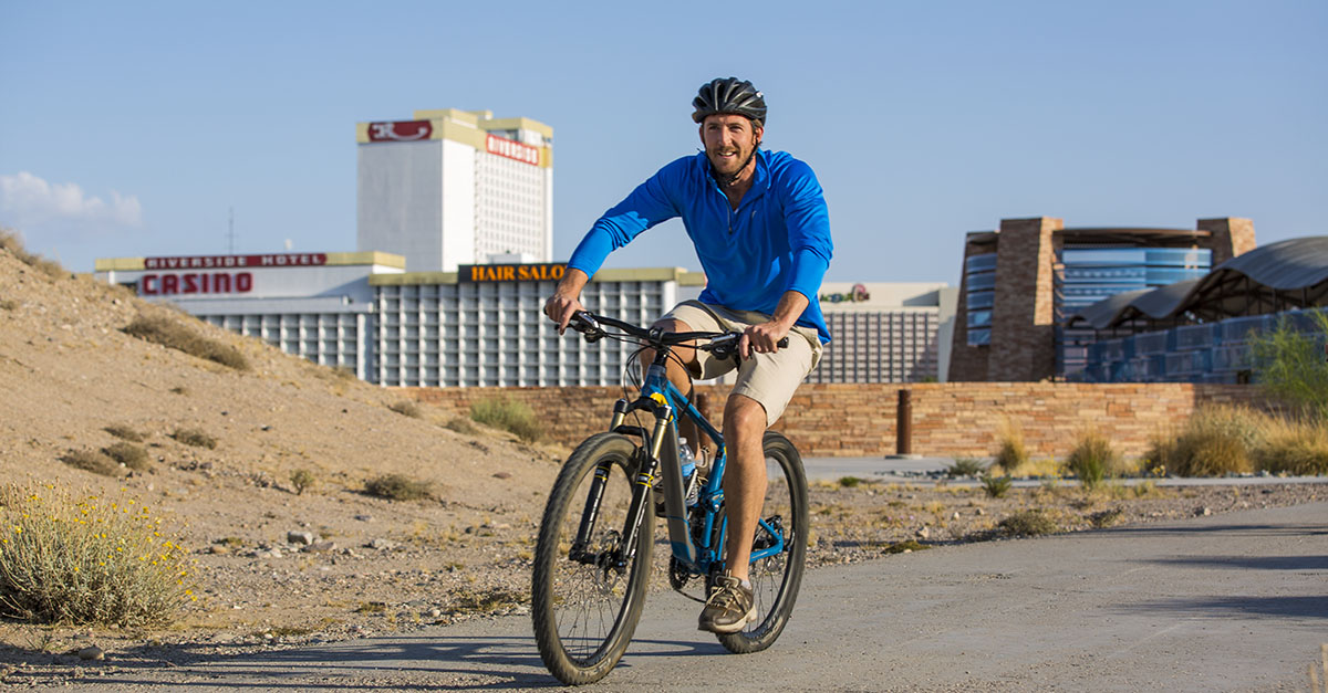 A man bikes on a paved path with casinos in background.
