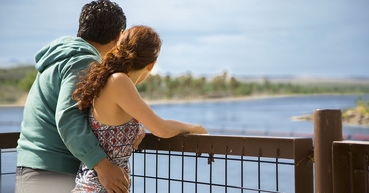 A man and woman lean on a railing as they look at a river.