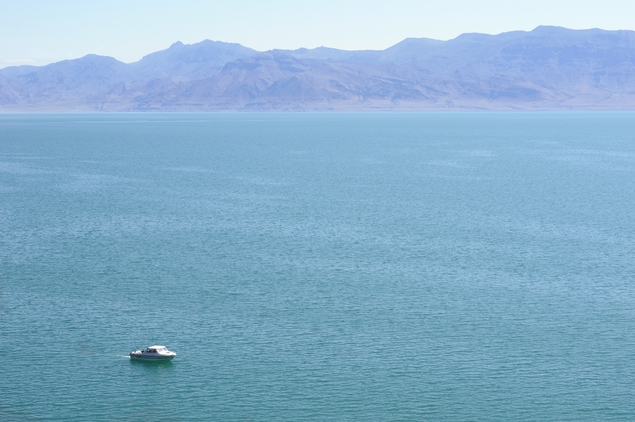 A lone fishing boat on a vast turquoise lak.e