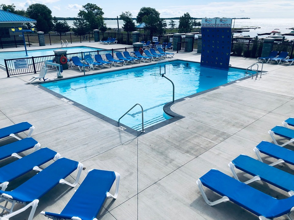 Blue deck chairs arrayed around a rectangular swimming pool.