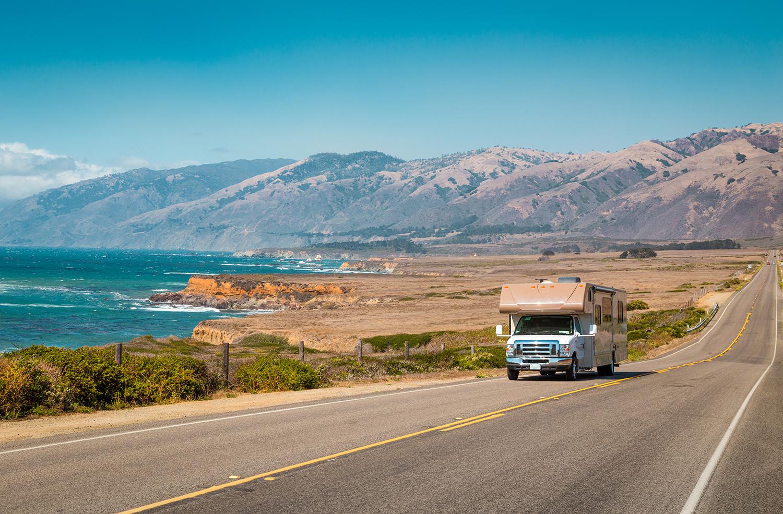 spring trip —Motorhome driving along a coastal road.