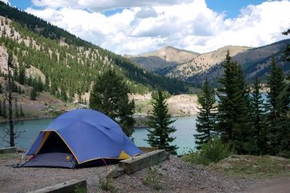 Blue pup tent near the shore of a lake.