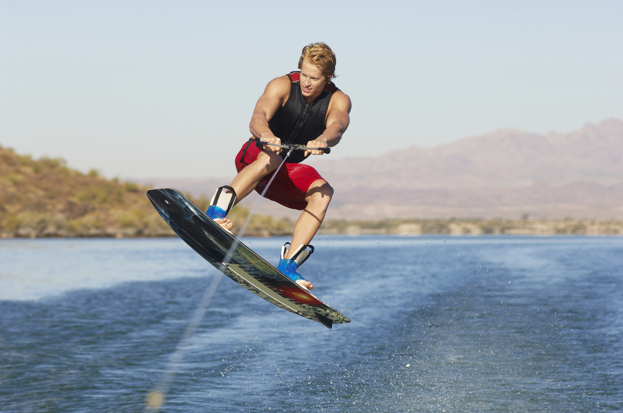 A young guy gets air while wakeboarding