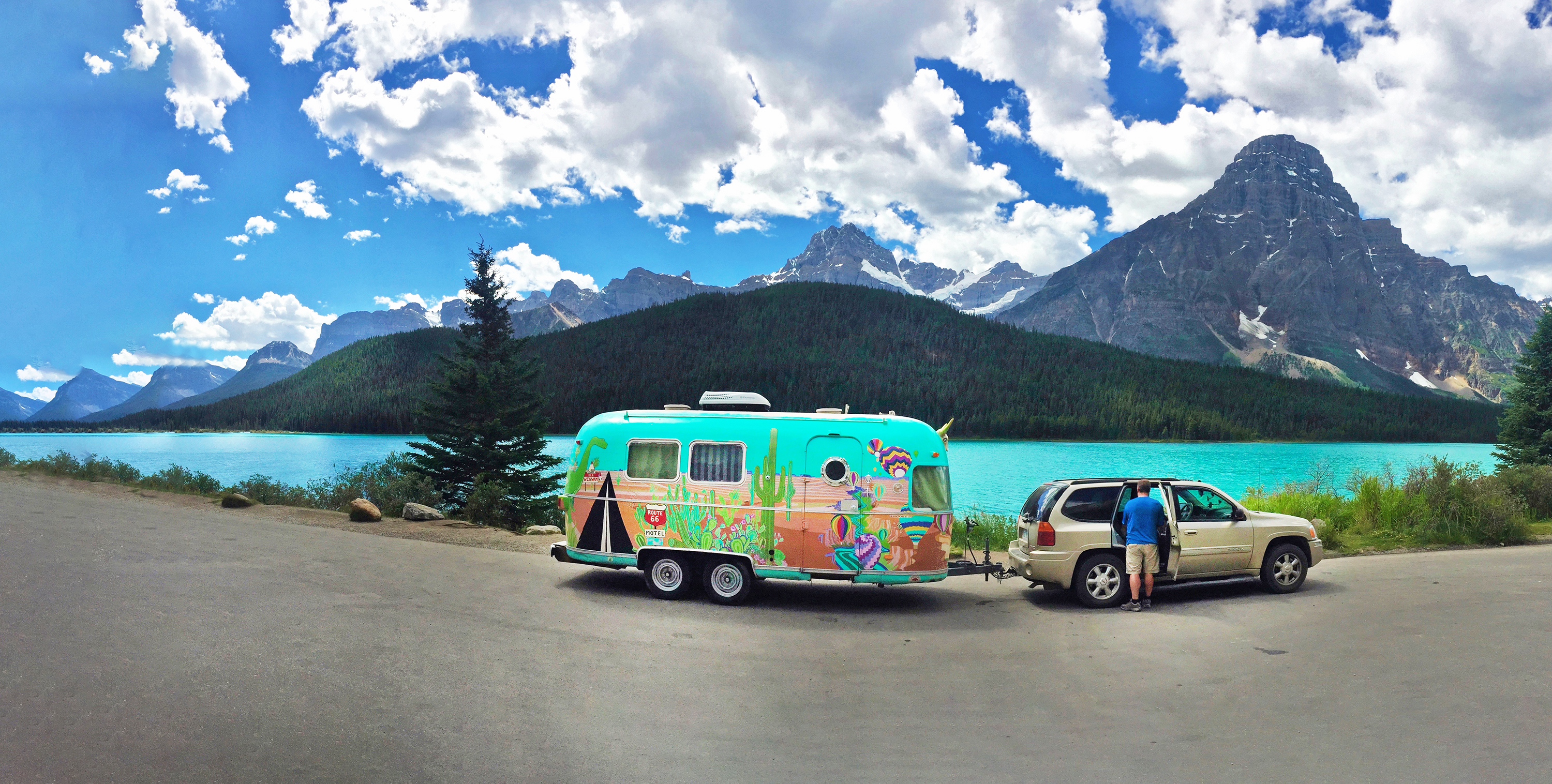 Banff and Jasper National Parks — A colorful airstream and tow vehicle parked in front of a turquoise lake.