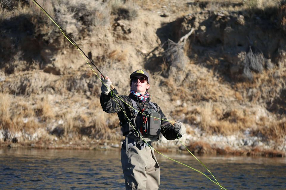 Woman preparing to cast a line during fly-fishing.