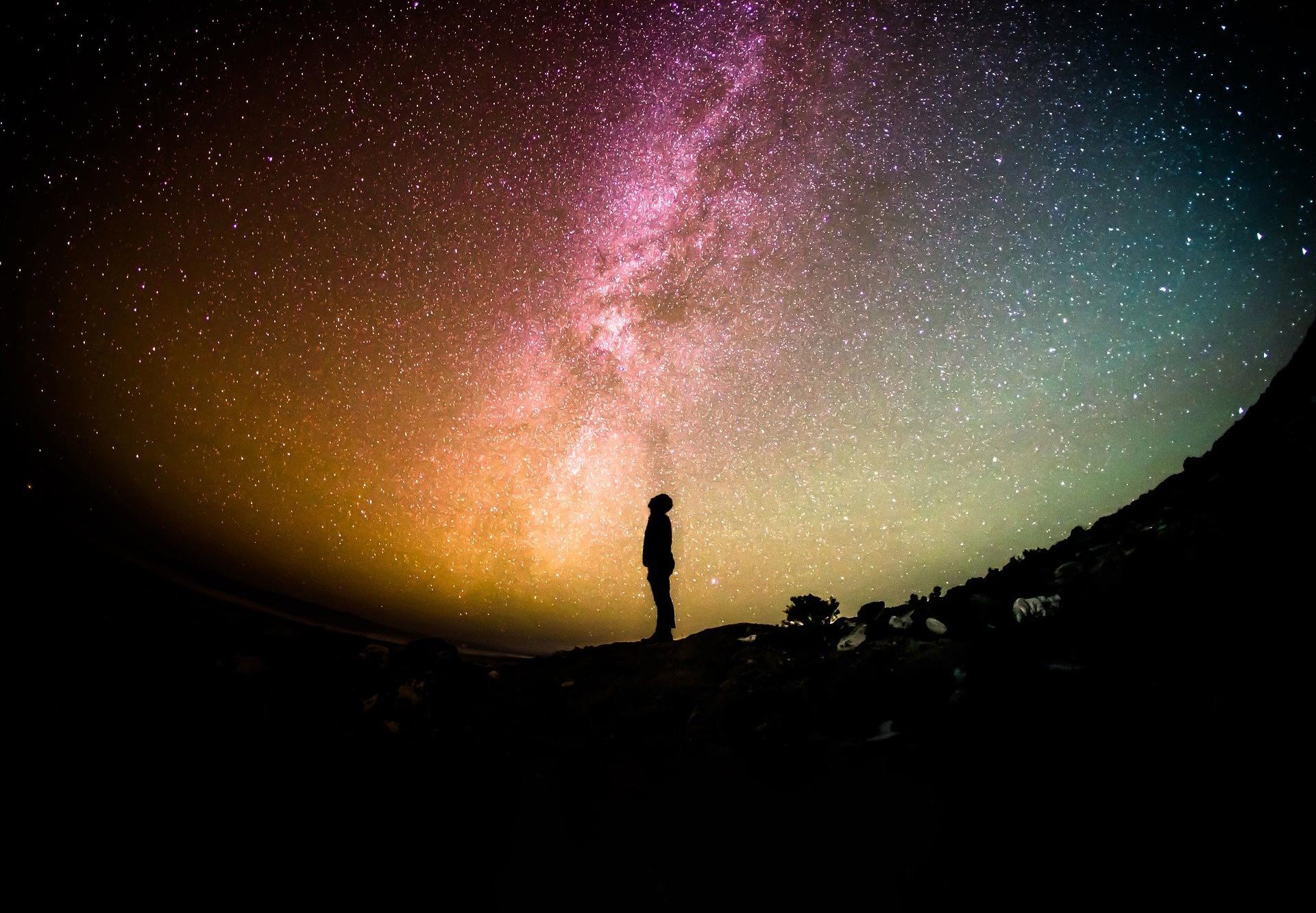A lone figure looks up an a starry sky.