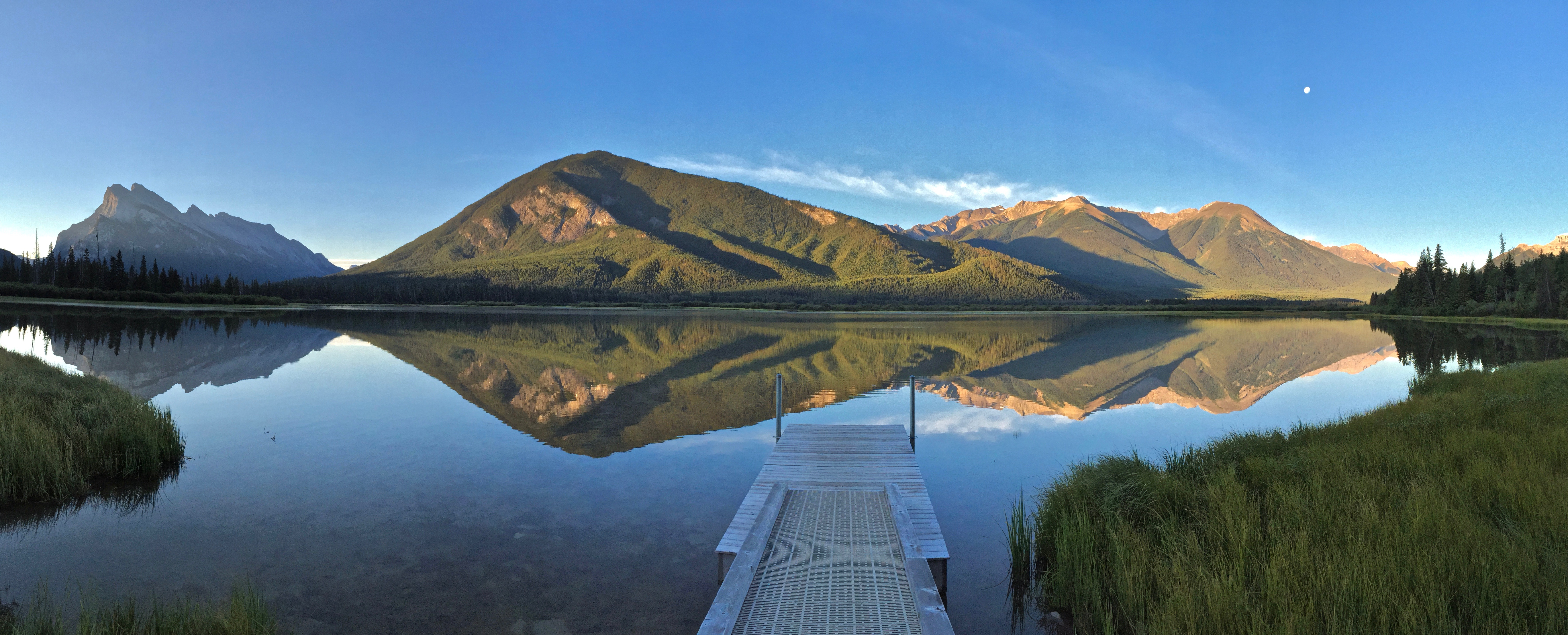 A green mountain reflected on a smooth lake surface; dock in foreground.