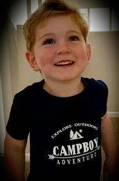 A boy wearing a black t-shirt with the Campboy logo on it