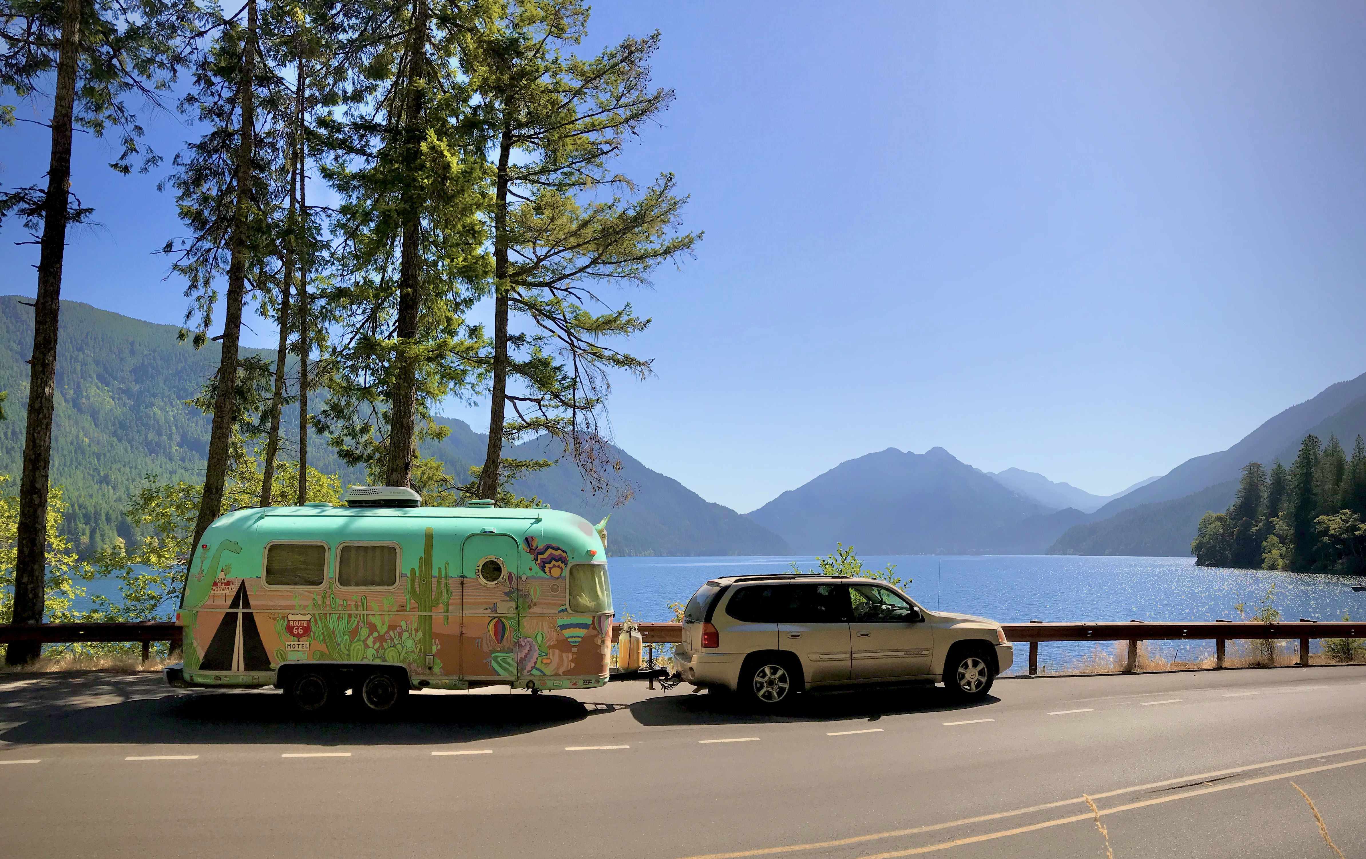 Colorful trailer parked on a lakeshore.