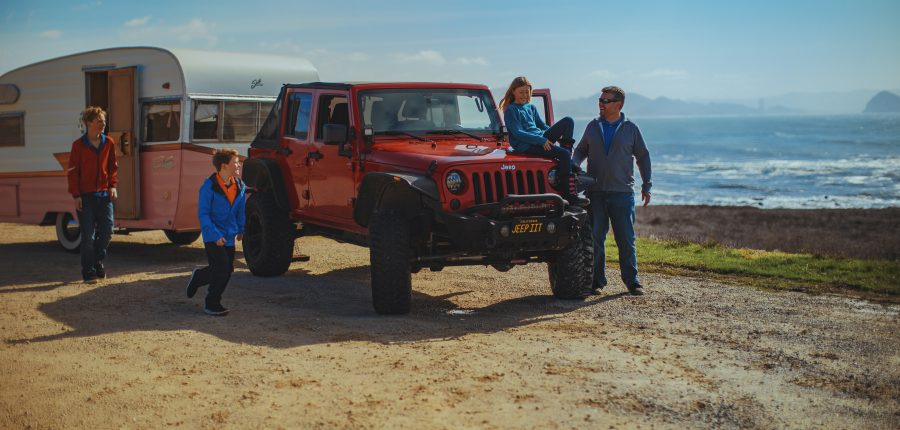 A family gathered around a red jeep hitched to a trailer.