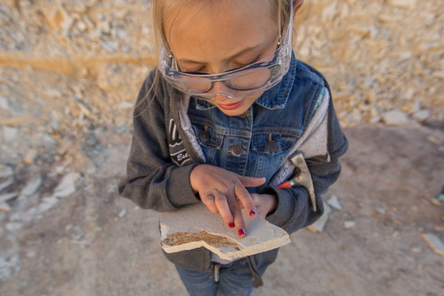 A girl examines a fossil against a background of loose rock.