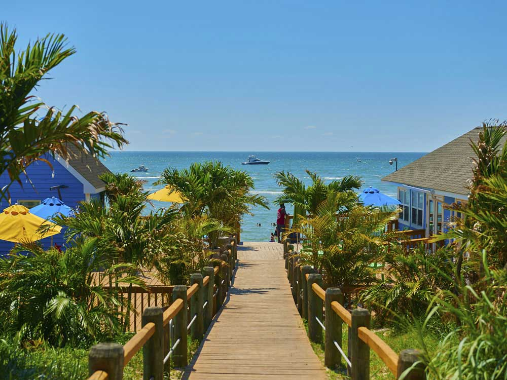 A wooden walkway flanked by colorful beach houses and palm trees toward the beach.