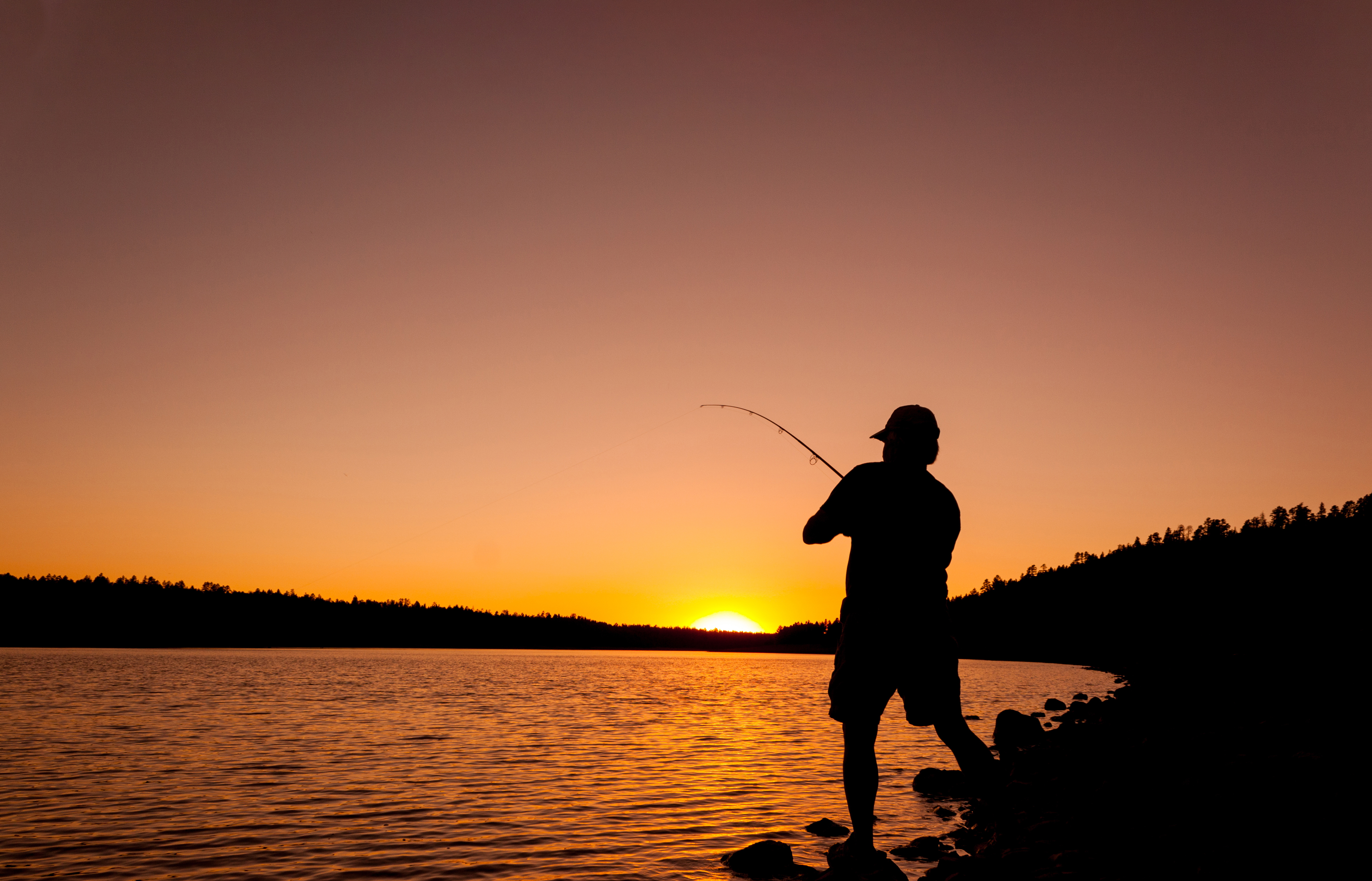 Man casts a line as the sun rises on the horizon.