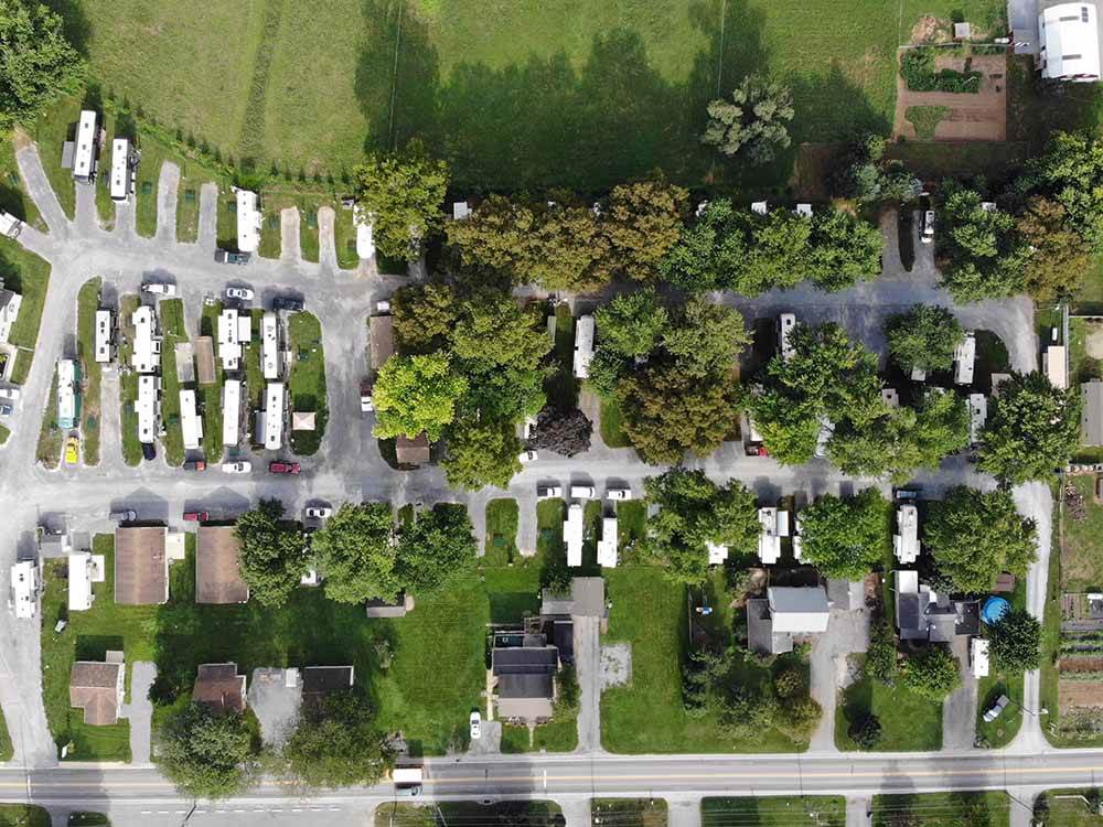 Aerial shot of RV park amid lush lawns and trees.