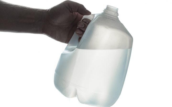 Hand holding 1 gallon plastic bottle of drinking water